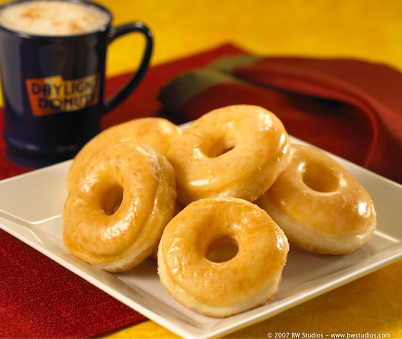 Image of a plate of donuts with coffee in the background